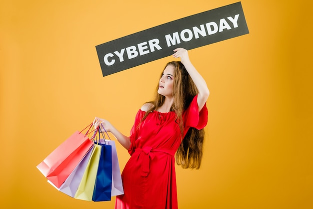 Excited young woman has cyber monday sign with colorful shopping bags isolated over yellow