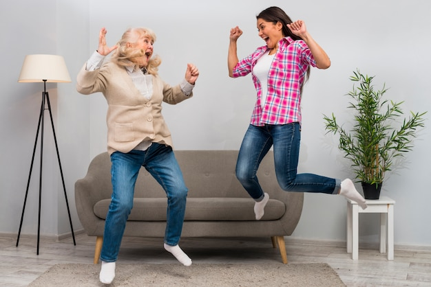 Excited young woman and her mother jumping in air at home