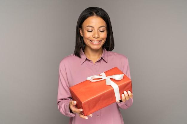 흥분한 젊은 여성이 크리스마스나 새해 휴가를 위해 선물 상자를 들고 현재를 보고 있는 행복한 여성