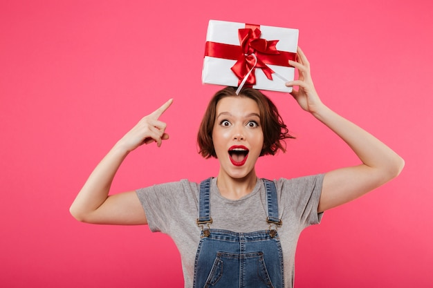 Excited young woman holding gift box pointing.