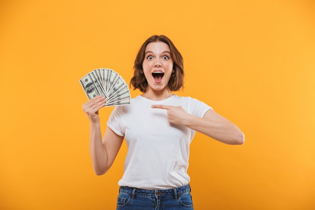 Excited young woman holding money looking camera pointing.
