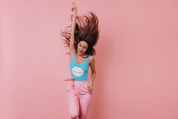 Возбужденная молодая женщина в синей майке танцует и смеется с поднятой рукой
