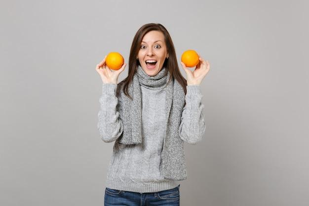 Возбужденная молодая женщина в сером шарфе свитера, держащая апельсины, изолированные на сером фоне, студийный портрет. здоровый образ жизни моды, искренние эмоции людей, концепция холодного сезона. копируйте пространство для копирования.