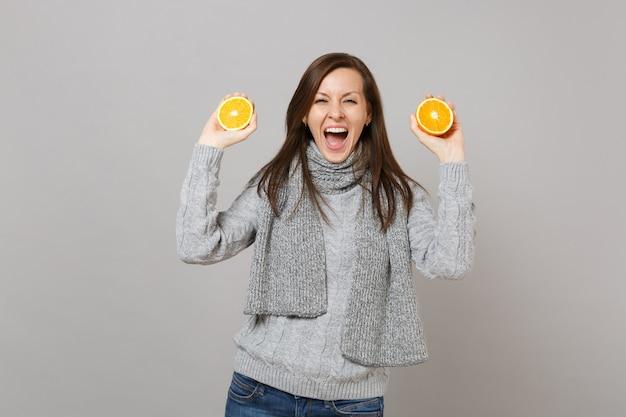 Возбужденная молодая женщина в сером свитере, шарфе держит рот широко открытым, удерживая апельсины, изолированные на сером фоне. люди здорового образа жизни моды искренние эмоции, концепция холодного сезона. копируйте пространство для копирования.