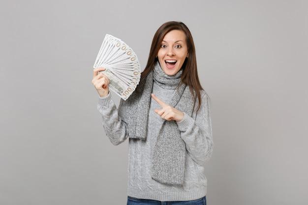 Возбужденная молодая женщина в сером свитере, указательный палец точки шарфа на кучу серий наличных денег банкнот долларов, изолированных на сером фоне. эмоции людей здорового образа жизни моды, концепция холодного сезона.