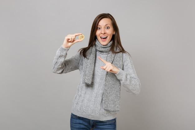 회색 스웨터를 입은 흥분한 젊은 여성, 스카프로 비트코인을 가리키는 스카프, 회색 벽 배경에 격리된 미래 통화. 건강한 패션 라이프스타일, 사람들의 진심 어린 감정, 추운 계절 개념.