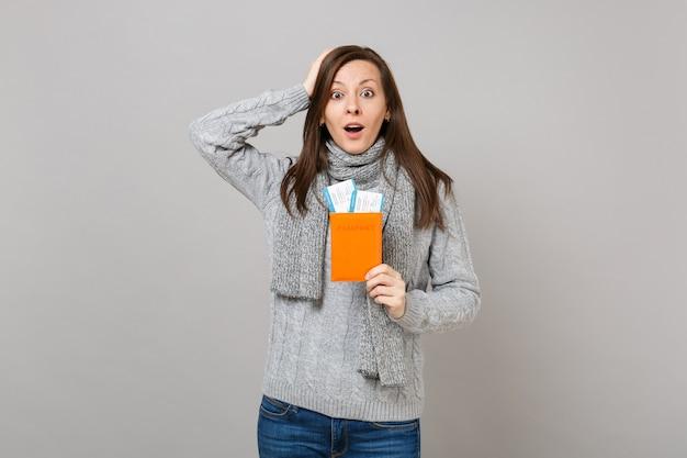 회색 스웨터를 입은 흥분한 젊은 여성, 스카프는 머리에 손을 얹고 여권을 들고 회색 배경에 격리된 탑승권. 건강한 패션 라이프스타일 사람들은 진심 어린 감정, 추운 계절 개념입니다.