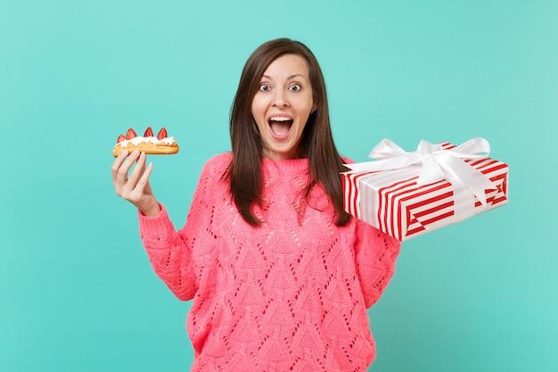ニットピンクのセーターで興奮した若い女性は、青い背景で隔離のギフトリボンとエクレアケーキ赤い縞模様のプレゼントボックスを保持します。バレンタインの女性の日の誕生日の休日のコンセプト。コピースペースをモックアップします。