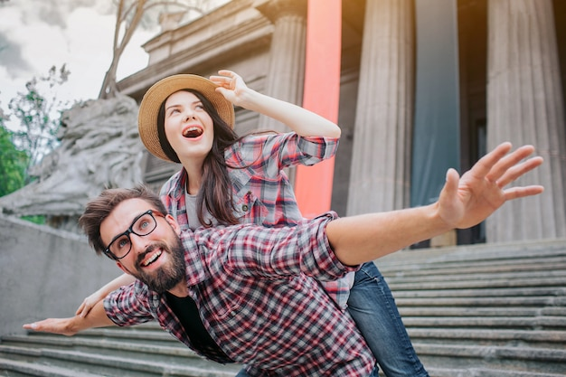 Excited young woman is lying on his boyfriend's back and holds hat with hand. she looks up. bearded young man keeps hands aside of body and look up too. they are happy.