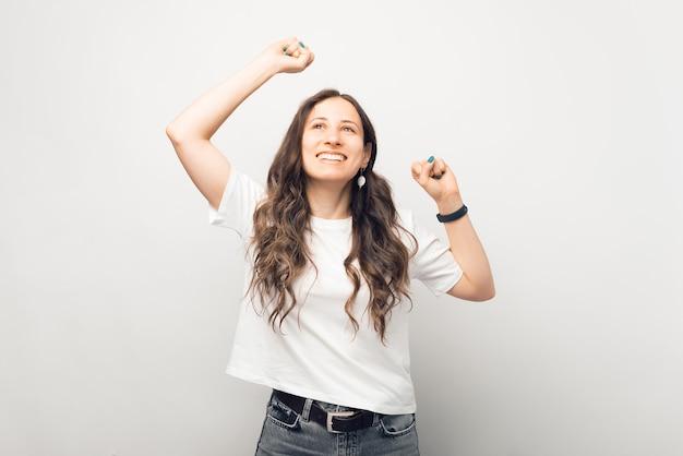 興奮した若い女性が見上げながら勝者のジェスチャーをしています。