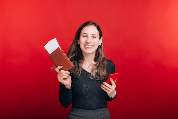 興奮した若い女性はパスポートとその中にいくつかのチケットを示し、赤いスペースに彼女の電話を持っています。