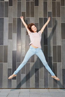Excited young woman jumping with arms raised