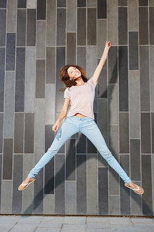 Excited young woman jumping with hands raised against wall