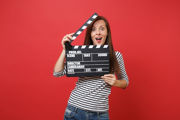 Excited young woman keeping mouth wide open looking surprised holding classic black film making clapperboard isolated on red background. people sincere emotions, lifestyle concept. mock up copy space.