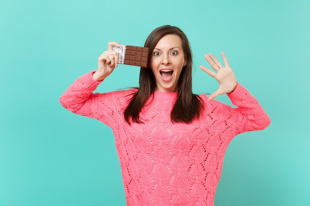 Excited young woman in knitted pink sweater hold in hand chocolate bar, showing palm keeping mouth wide open isolated on blue background, studio portrait. people lifestyle concept. mock up copy space.