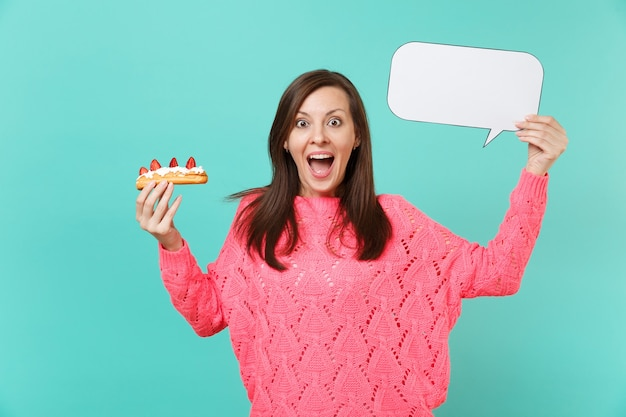 Excited young woman in knitted pink sweater holding eclair cake, empty blank say cloud speech bubble for promotional content isolated on blue background. people lifestyle concept. mock up copy space.