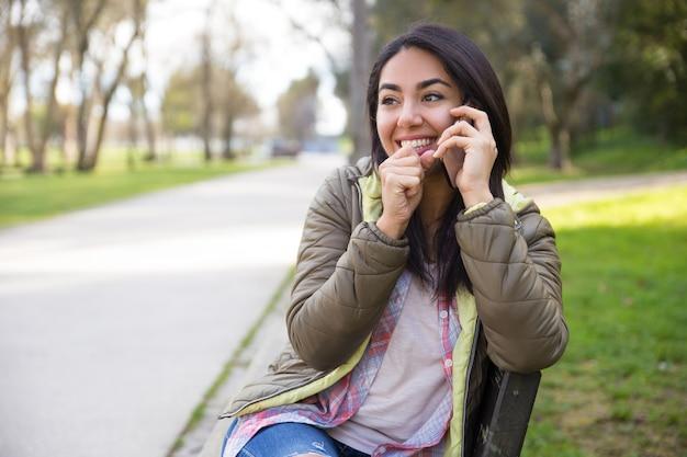 전화 통화하는 동안 웃고 흥분된 젊은 여성
