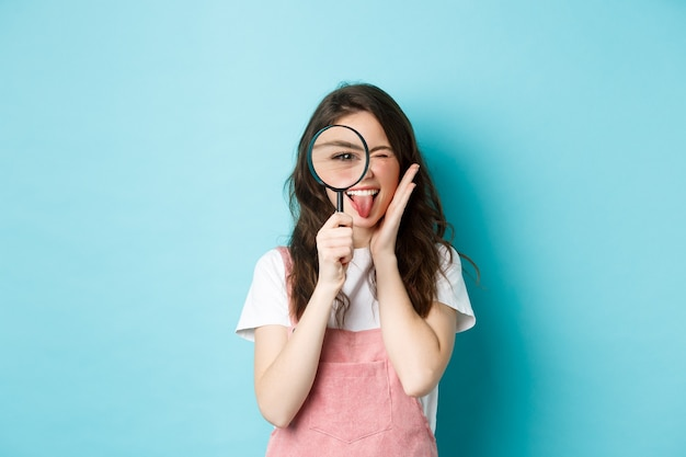 Excited young woman looks through magnifying glass, searching for someone, investigating, standing over blue background