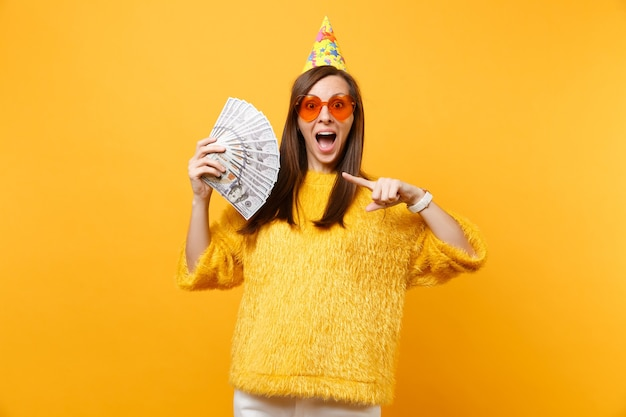 Excited young woman in orange heart glasses and birthday hat pointing index finger on bundle lots of dollars cash money, celebrating isolated on yellow background. people sincere emotions, lifestyle.