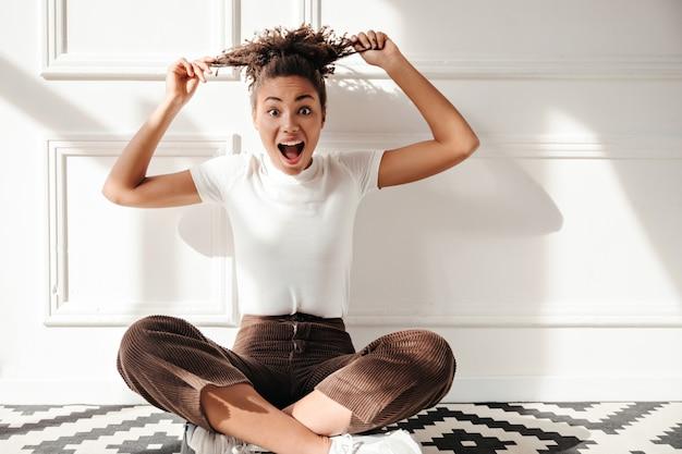 Возбужденная молодая женщина играет с вьющимися волосами