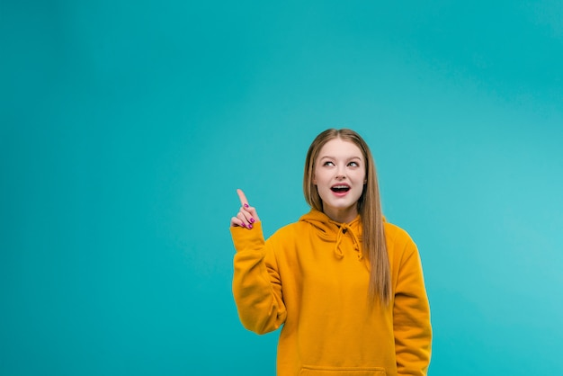 Excited young woman pointing at copyspace above her with her finger isolated over turquoise background