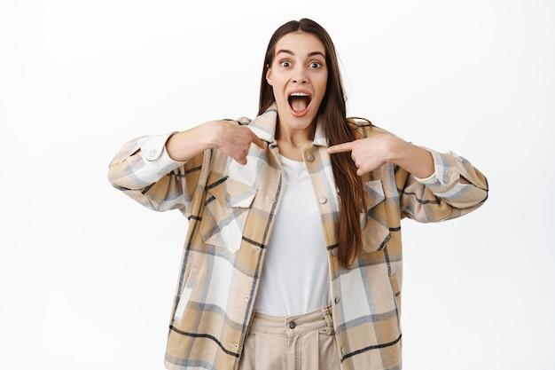 興奮した若い女性が自分を指さしている