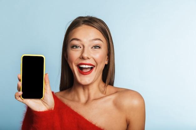 Возбужденная молодая женщина позирует изолированно, используя мобильный телефон, показывающий пустой дисплей.
