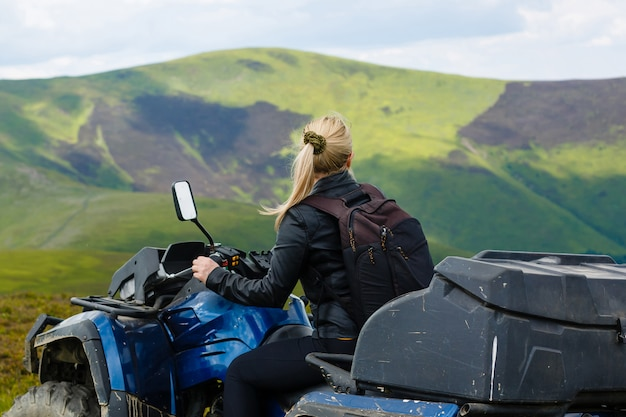 Excited young woman on quad bike. happy young woman driving all terrain vehicle in nature.