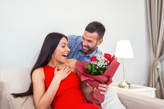 남편에게서 예기치 않은 빨간 장미 꽃다발을받는 흥분된 젊은 여성