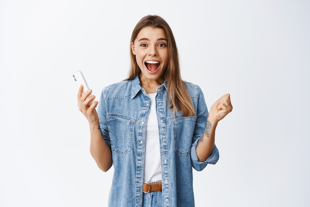 Eccitata giovane donna urla di sì e sorride stupita, tenendo in mano lo smartphone e fissando davanti, vincendo online, in piedi felice del successo contro il muro bianco
