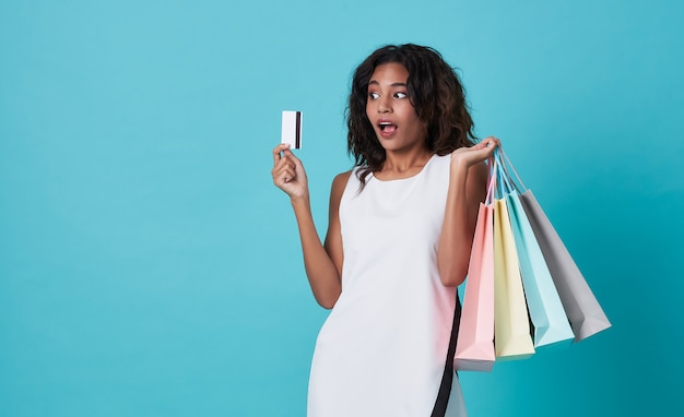 Excited young woman showing credit card and shopping bags isolated over blue