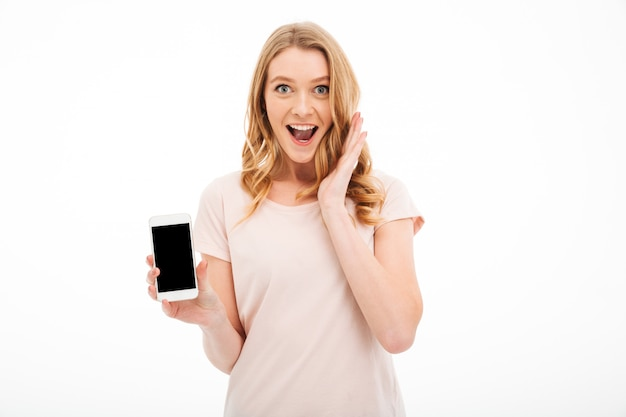 Excited young woman showing display of mobile phone.