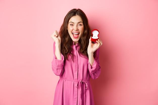 약혼 반지를 보여주는 흥분된 젊은 여성이 결혼을 축하하고, 행복하게 웃고, 결혼식에 대해 이야기하고, 결혼 제안을 받고, 분홍색 벽 위에 서 있습니다. 공간 복사