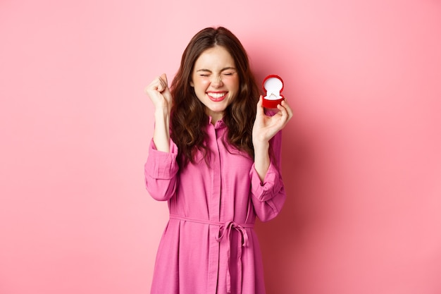약혼 반지를 보여주는 흥분된 젊은 여성이 결혼을 축하하고, 행복하게 웃고, 결혼식에 대해 이야기하고, 결혼 제안을 받고, 분홍색 벽 위에 서 있습니다.
