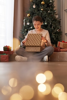 Excited young woman sitting with crossed legs near decorated tree and opening christmas gift box