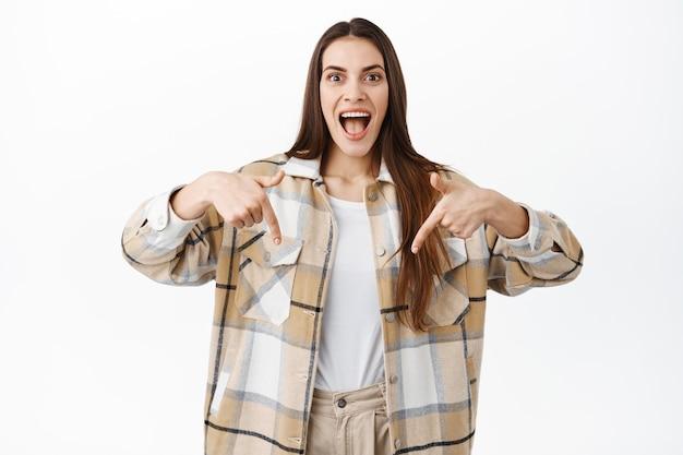 興奮した若い女性が笑顔で驚いて幸せそうな顔で下を向いて、素晴らしい新しいプロモーション取引を示し、白い壁の上に立って、素晴らしいオファーでロゴバナーを指さします