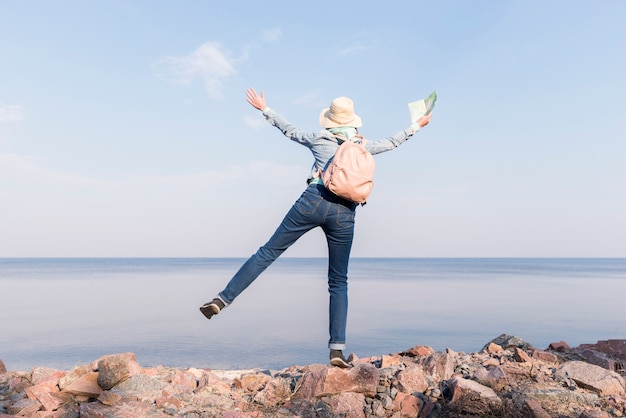 Excited young woman standing on top of rock holding map in hand overlooking the sea against blue sky