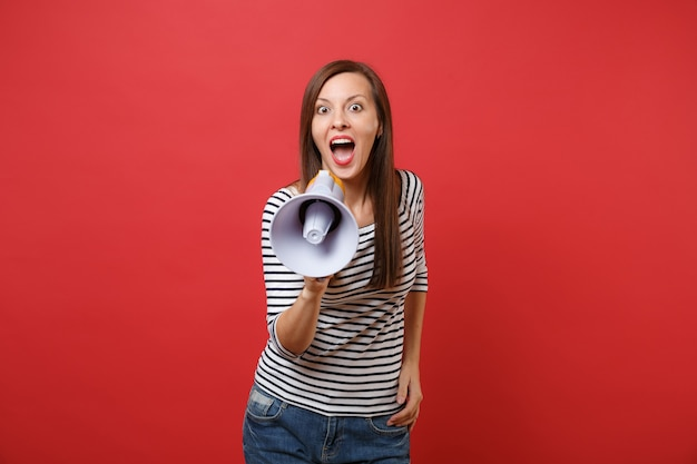 Excited young woman in striped clothes screaming on megaphone keeping mouth wide open looking surprised isolated on red wall background. people sincere emotions, lifestyle concept. mock up copy space.