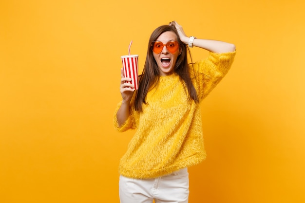 Excited young woman in sweater, heart orange glasses clinging to head holding plastic cup with cola or soda isolated on yellow background. people sincere emotions, lifestyle concept. advertising area.