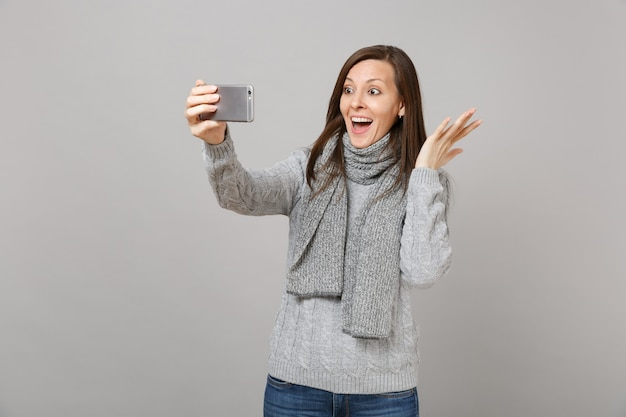 Excited young woman in sweater, scarf spreading hands, doing selfie shot on mobile phone, making video call isolated on grey background. healthy fashion lifestyle people emotions cold season concept.