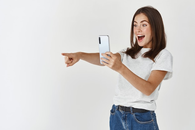 Excited young woman taking picture on mobile phone, pointing left at product and smiling, recording video on smartphone, white wall