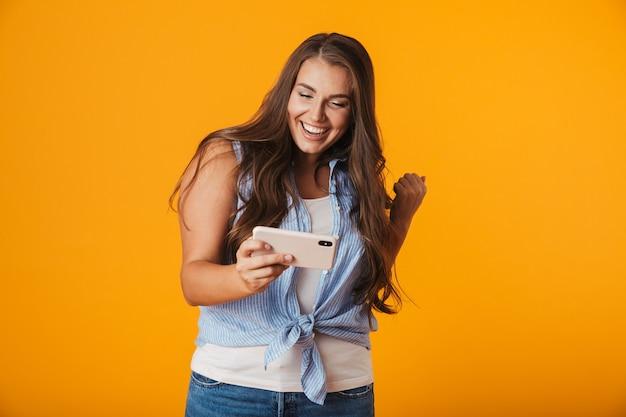 Возбужденная молодая женщина, используя мобильный телефон, играет в игры