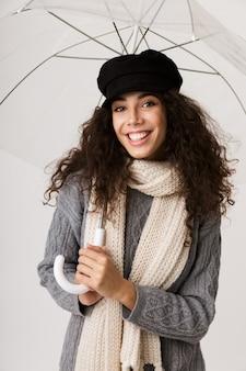 開いた傘を持って、白い壁の上に孤立して立っている秋の服を着て興奮した若い女性