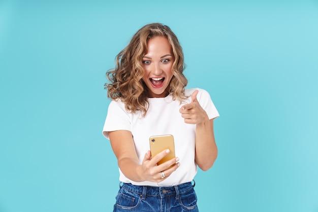 Возбужденная молодая женщина в повседневной одежде, стоя изолированной на синем, с помощью мобильного телефона