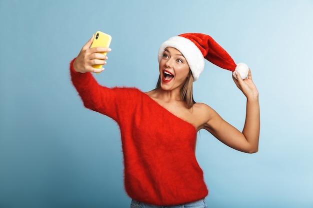 크리스마스 모자를 쓰고 흥분된 젊은 여성, 휴대 전화로 셀카를 가져 가라.