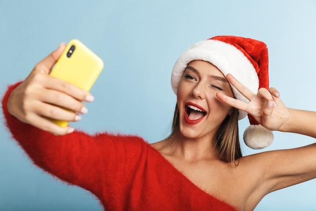 クリスマスの帽子をかぶった興奮した若い女性は、携帯電話で自分撮りをします。