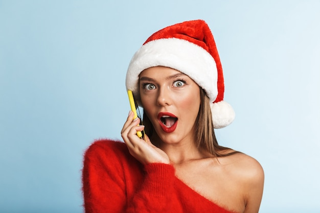 Excited young woman wearing christmas hat, talking by mobile phone.