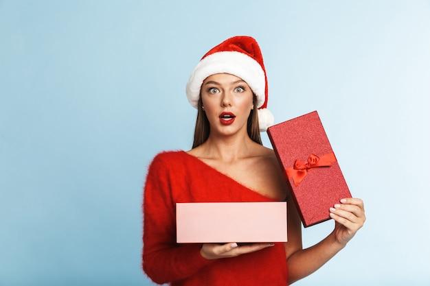 Возбужденная молодая женщина в красной шляпе санта-клауса стоит с открытой подарочной коробкой