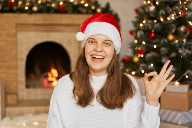 Excited young woman wearing santa claus hat and jumper gesturing okay sign,  with excitement, showing her teeth, posing indoor with fireplace and x-mas tree .