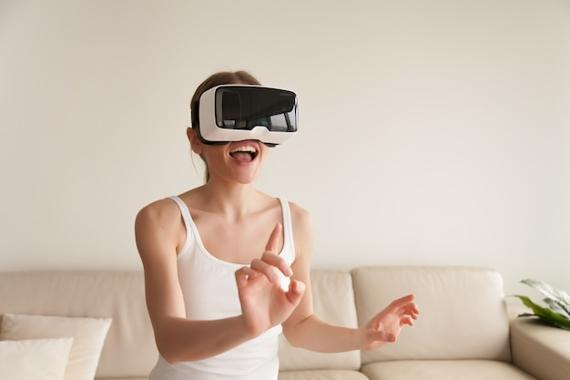 Excited young woman wearing vr headset touching virtual reality